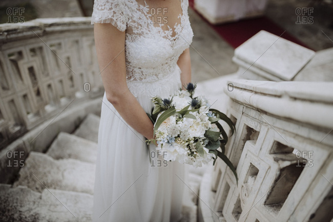 Bride standing on staircase holding wedding bouquet