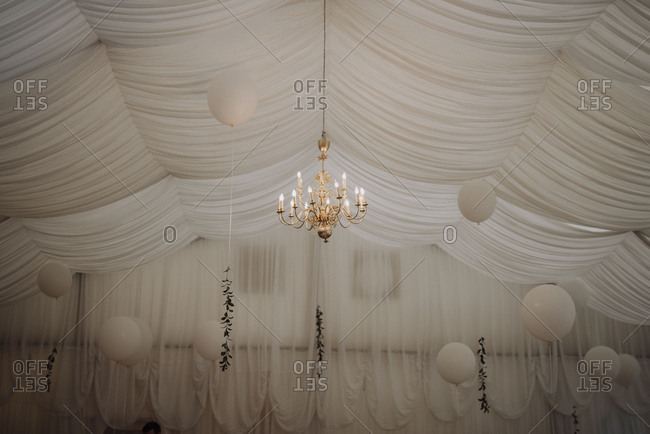 White balloons and chandelier hanging beneath draped ceiling at wedding