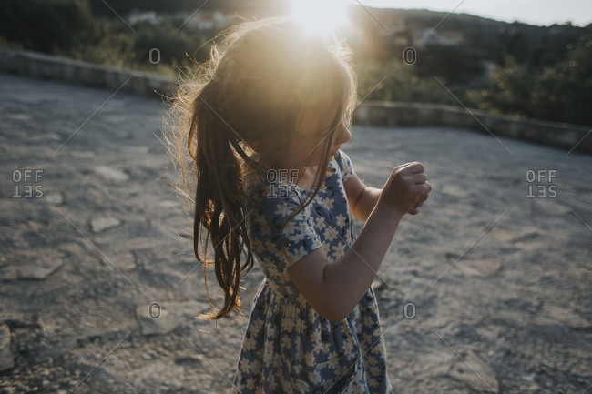 Girl making a fist walking on a road in Crete