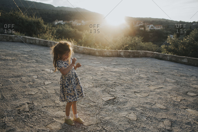 Girl playing with stones standing on a road in Crete