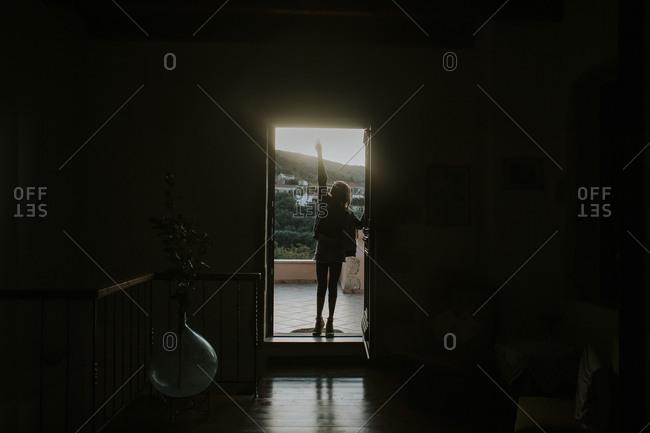 Girl standing in doorway reaching up