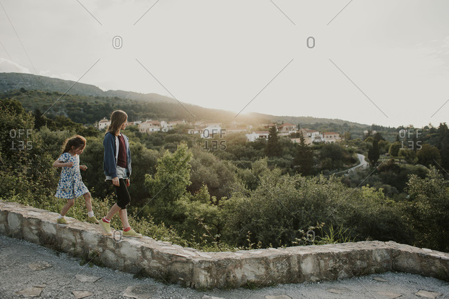 Sisters walking on a stone wall together in Crete