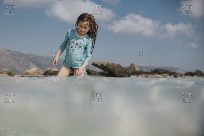 Girl wading in the water on the beach in Crete