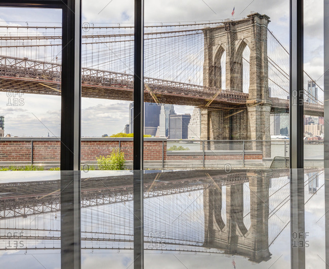 A glass interior space with views of Brooklyn Bridge Park