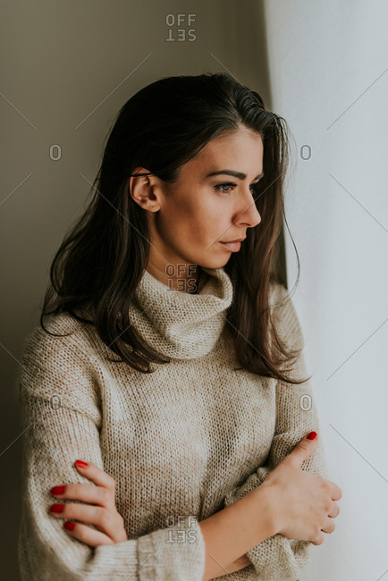 Beautiful black hair woman in  early thirties wearing beige sweater looking soft and gentle