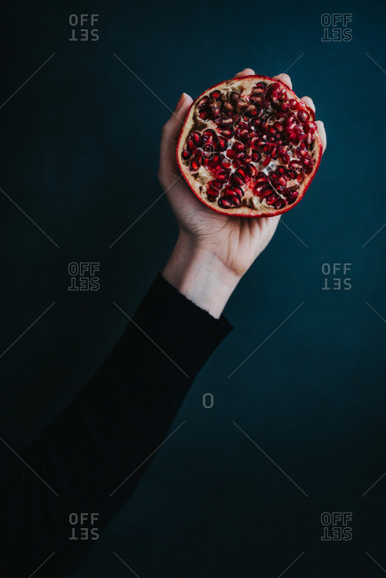 Hand holding pomegranate cut in half on dark background