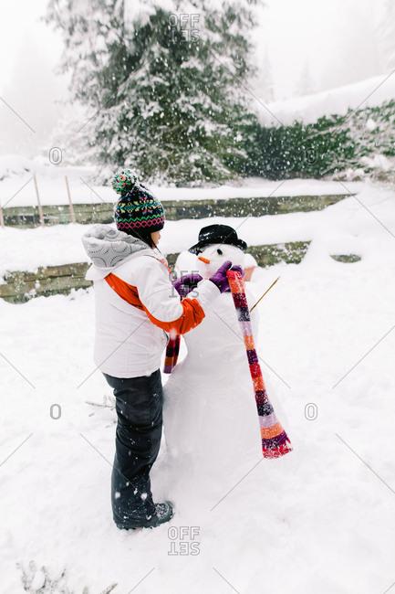 A girl building a snowman