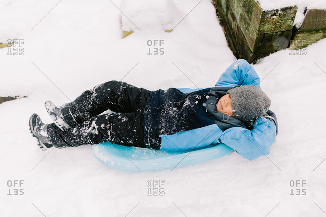 A boy rests on a winter sled