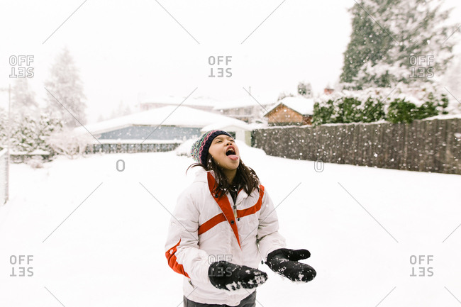 A girl catches snowflakes