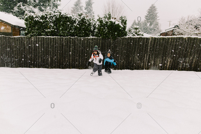 A brother and sister play in snow