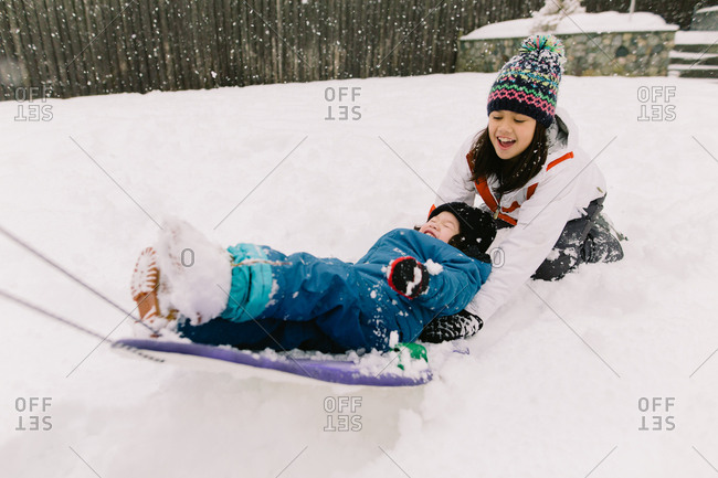 A girl pulls her brother on a sled
