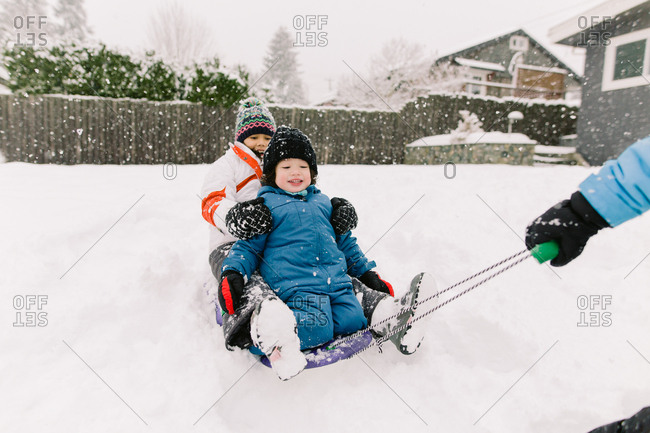 A brother and sister riding a sled together