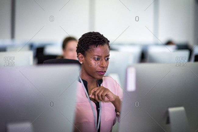 Businesswoman using computer in crowded office