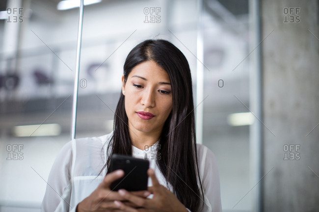 Businesswoman using smartphone in an office