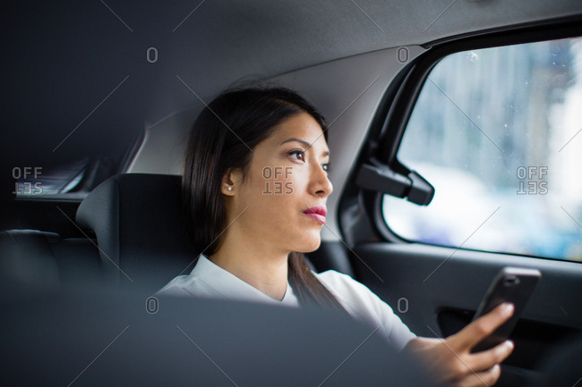 Businesswoman looking out of window of taxi cab