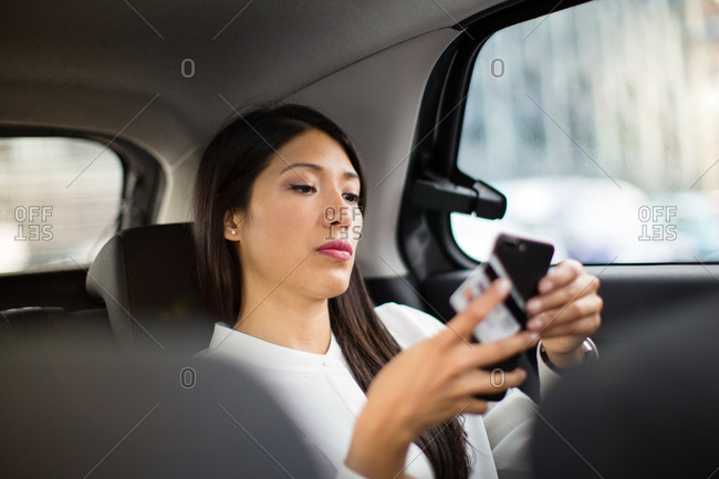 Businesswoman paying via app for taxi cab ride