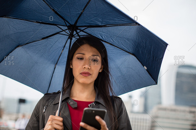 Businesswoman in city holding umbrella looking at smartphone