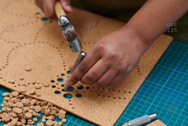 London, England - December 15, 2015: Craftswoman punching patterns in cork fabric