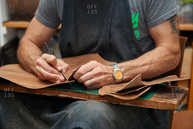 London, England - December 15, 2015: Shoemaker cutting out a pattern from a piece of leather