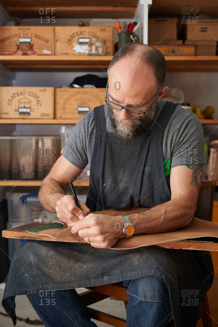 London, England - December 15, 2015: Shoemaker cutting a pattern from a piece of leather