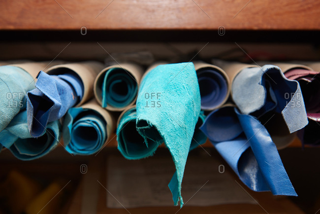 Rolls of blue leather fabric in a shoemaker's workshop