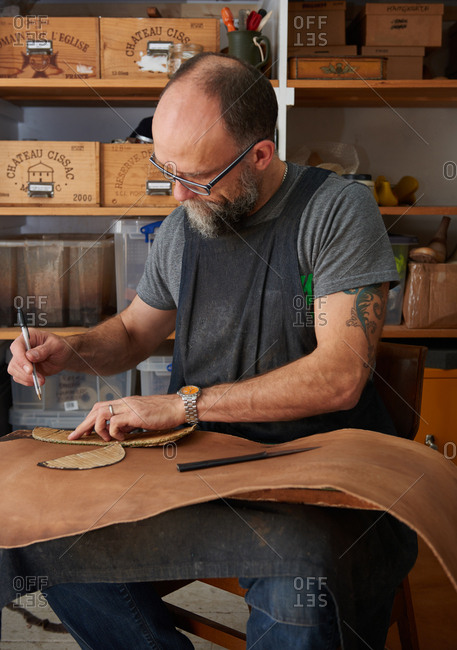 London, England - December 15, 2015: Shoemaker marking out a pattern piece on leather