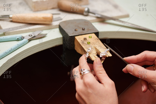 London, England - December 15, 2015: Jeweler files a pair of handmade earrings on a workbench