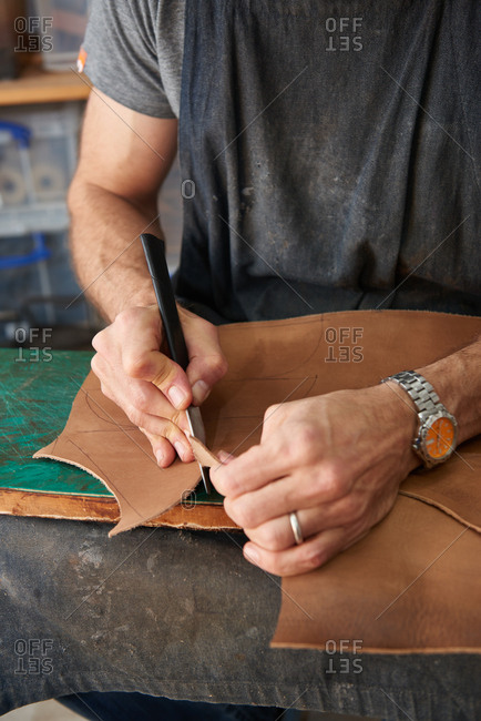 Shoemaker cutting out pattern pieces from leather