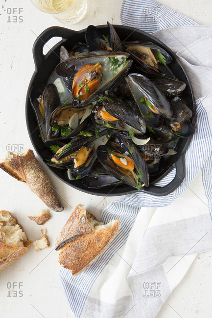 Mussels in pan by baguette
