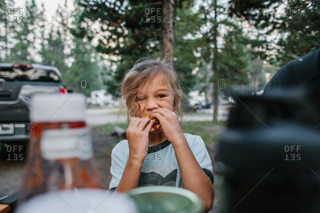 Boy eating at campsite picnic table