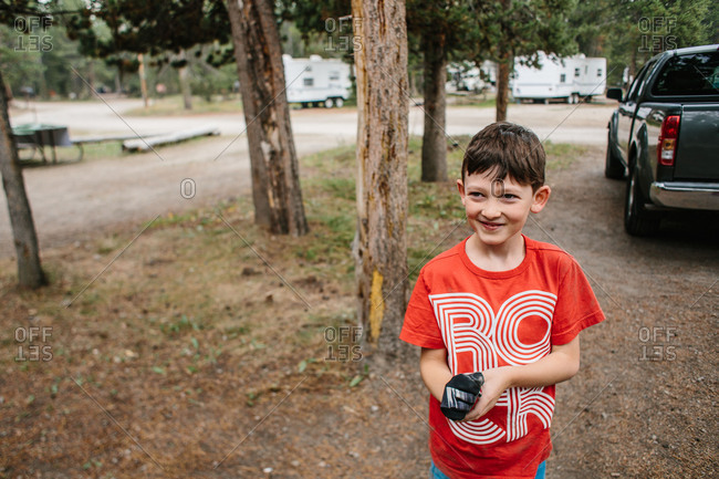 Boy with work gloves in camp site