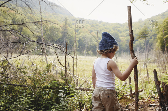Little boy in blue cap stands with stick