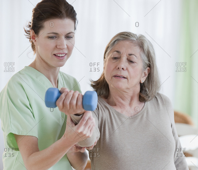 Physical therapist helping senior woman
