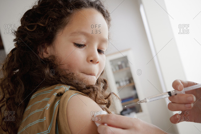 Girl (8-9) having vaccination