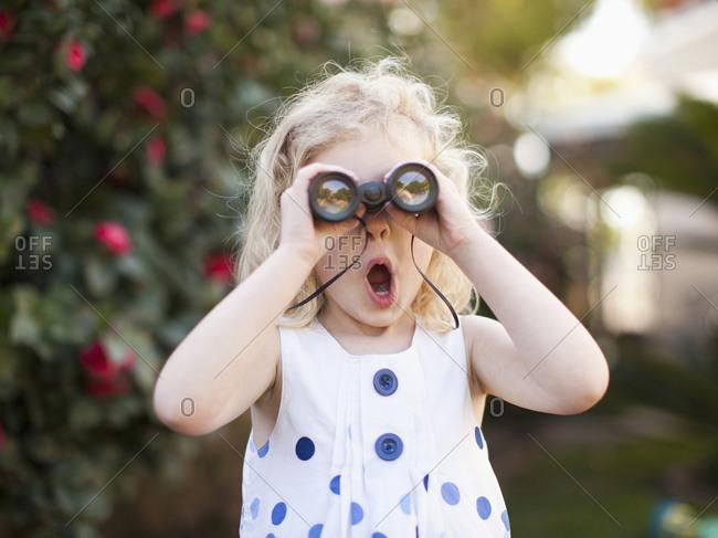 Surprised young girl (4-5) looking through binoculars
