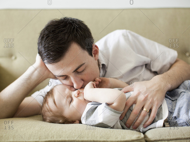 Father and baby boy (6-11 months) lying on sofa
