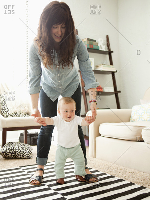 Young mother assisting baby boy (6-11 months) in his first steps
