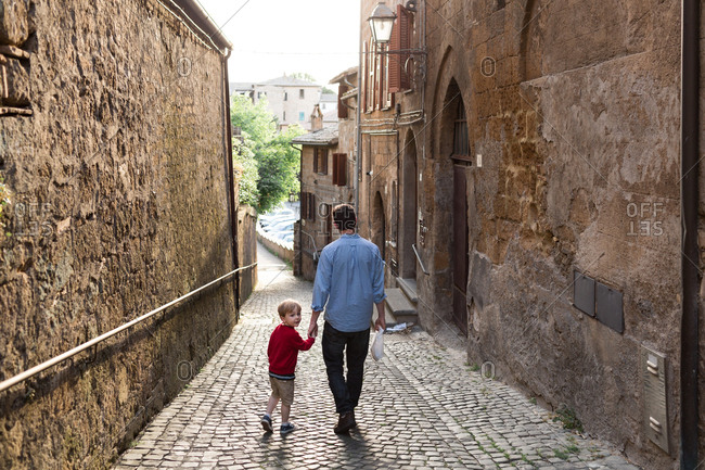 Father and son holding hands walking down cobblestone street