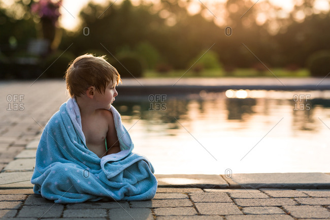 Young boy wrapped in towel sitting by pool