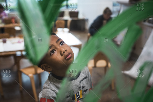 Boy looks up at painted glass during arts and crafts