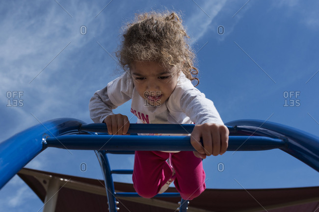 Toddler girl climbs on playground bars