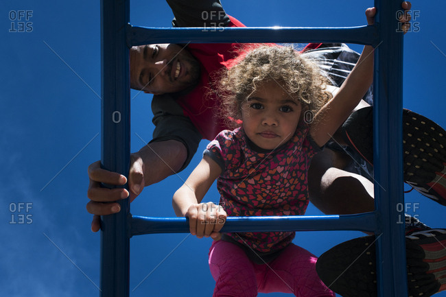 Father and daughter climb playground equipment