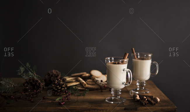 2 glasses of eggnog on a wooden table with holiday decorations against a solid gray wall
