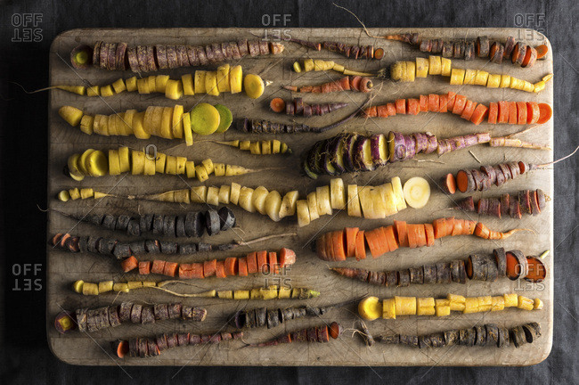 An array of rainbow carrots in many shapes and colors, all chopped finely on a worn wood chopping block