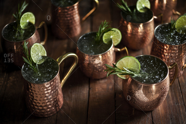Multiple moscow mule drinks in copper mugs on rustic wood surface with rosemary and lime garnishes