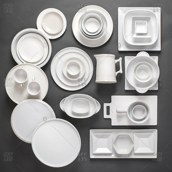 Assorted variety of white porcelain dinnerware laid out in a graphic, organized way on a gray background