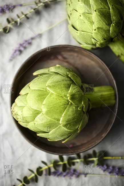 Artichokes in metal tin with flowers on a natural linen surface