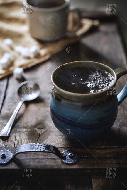 Handmade stone mug of steaming hot tea on rustic wood serving tray with morning light coming in behind