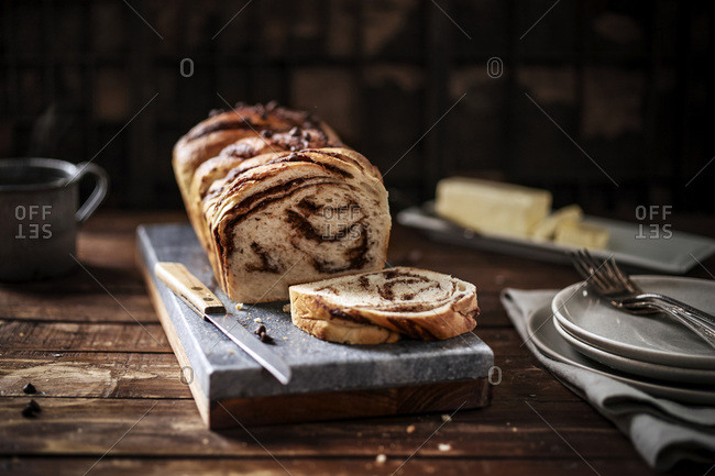 Warm loaf of chocolate braided bread on a marble board in a rustic wood setting