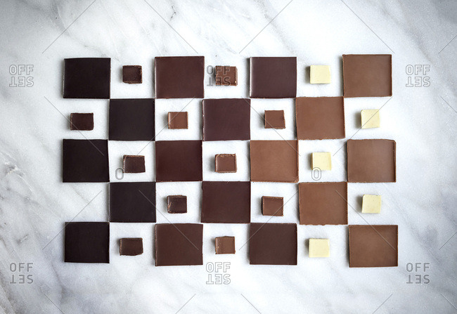 A geometric layout of chocolate squares in ombre pattern from dark chocolate to white chocolate on a marble surface